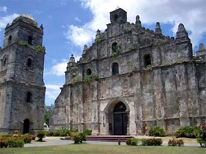 Ground-level photo of the Paoay Church's facade and its bell tower.